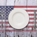 A dining scenario of a white plate and silver cutlery, shot overhead, on top of a worn rustic white wooden surface, featuring a stenciled flag.